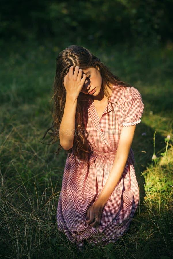 Ung flicka i tappningklänningen som sitter på gräs Brunett som täcker hennes ögon från solen Härlig nymf i skog arkivbild