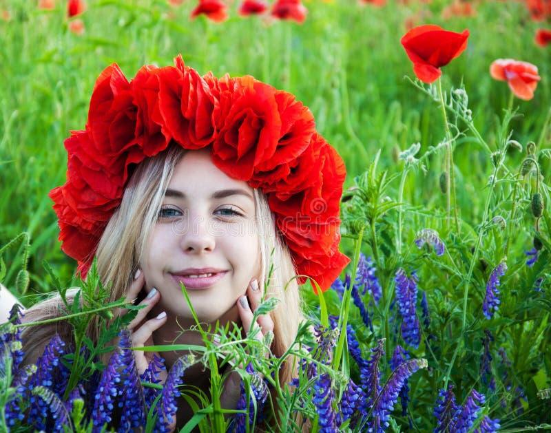 Ung flicka i vallmofältet royaltyfri foto