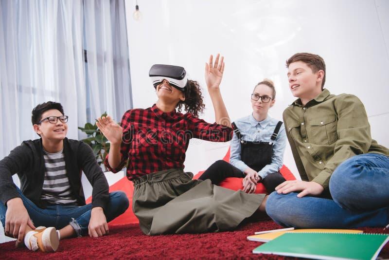 ung flicka i virtuell verklighetexponeringsglas som sitter på matta royaltyfria bilder