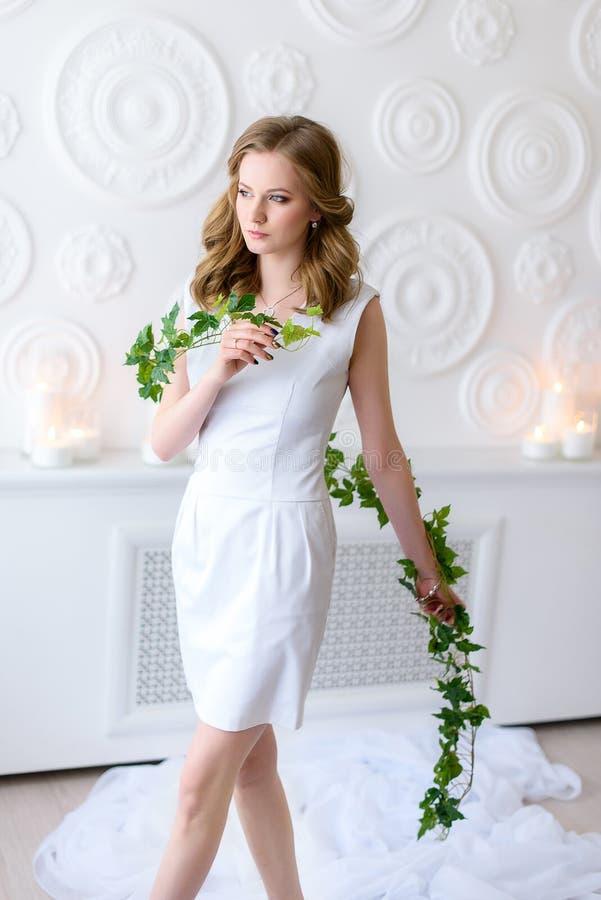 Ung flicka i vitt gå i ett ganska rum med en lång ny grön filial i hennes händer, allvarlig ögonkast åt sidan royaltyfri fotografi