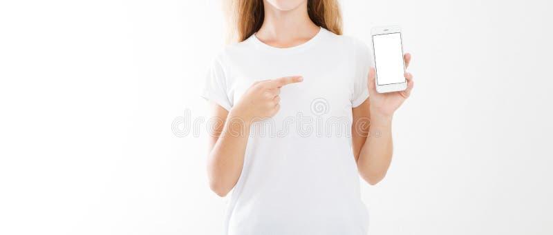 Ung flicka kvinna i t-skjorta som pekar fingret på mobiltelefonen för tom skärm som isoleras på vit bakgrund holdingen för bakgru arkivfoto