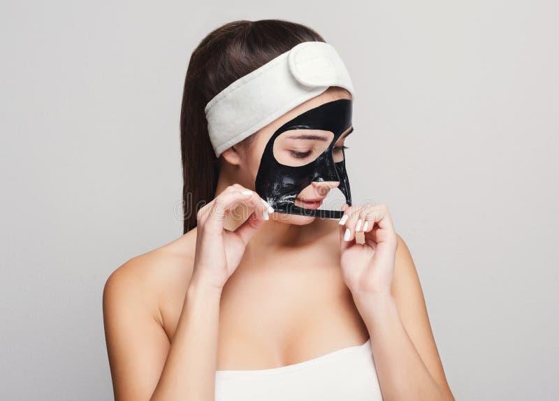 Ung flicka med att rena maskeringen för svart framsida royaltyfri foto