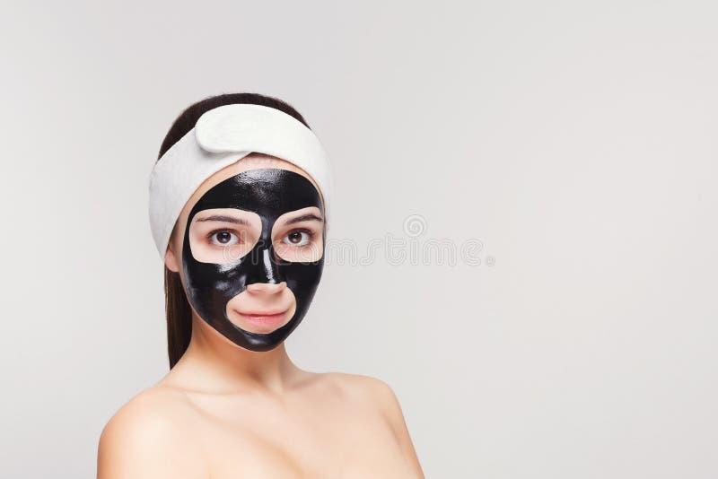 Ung flicka med att rena maskeringen för svart framsida royaltyfria foton