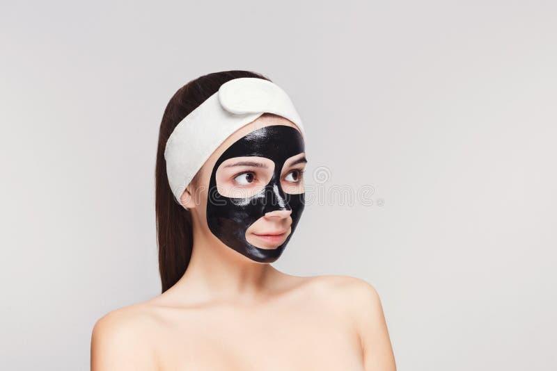 Ung flicka med att rena maskeringen för svart framsida royaltyfria bilder
