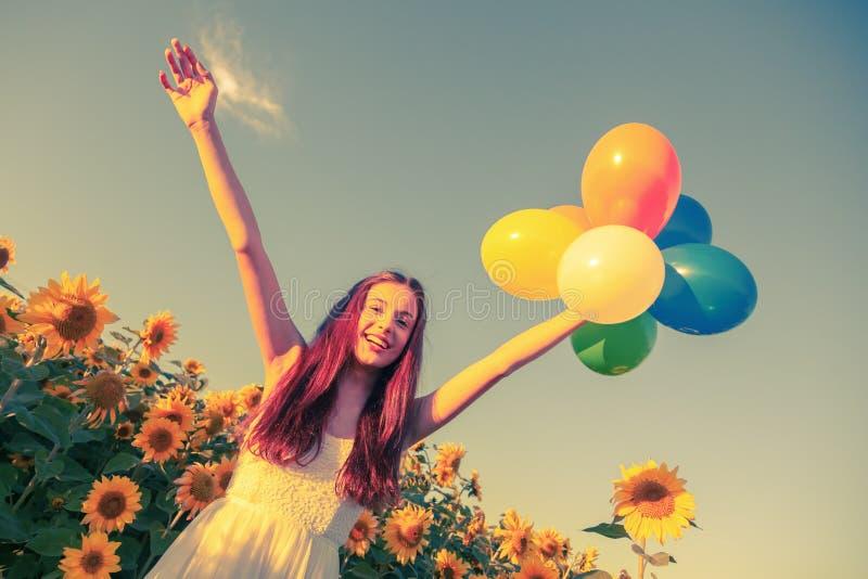 Ung flicka med ballonger på ett solrosfält arkivfoton