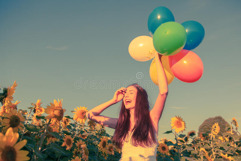 Ung flicka med ballonger på ett solrosfält royaltyfri bild