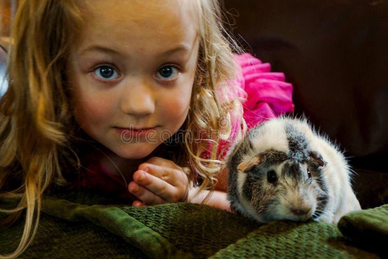 Ung flicka med den älsklings- försökskaninen arkivfoto
