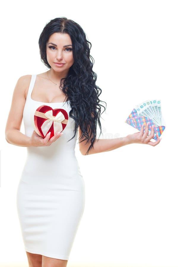 Ung flicka med den röda hjärta-formade gåvaasken med ryska pengar i den vita klänningen på vit bakgrund royaltyfri foto