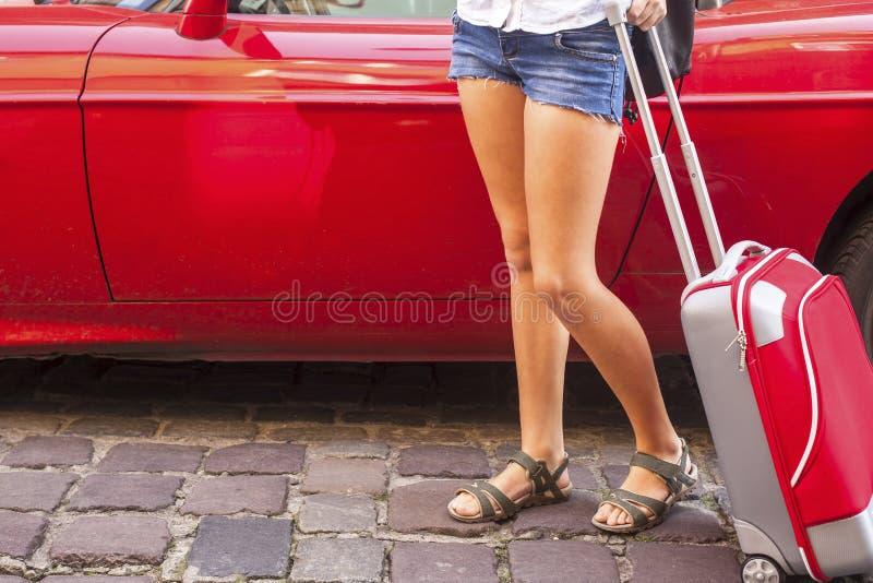 Ung flicka med den röda resväskan nära bilen arkivbild