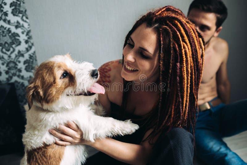Ung flicka med dreadlocks som rymmer en hund arkivbild