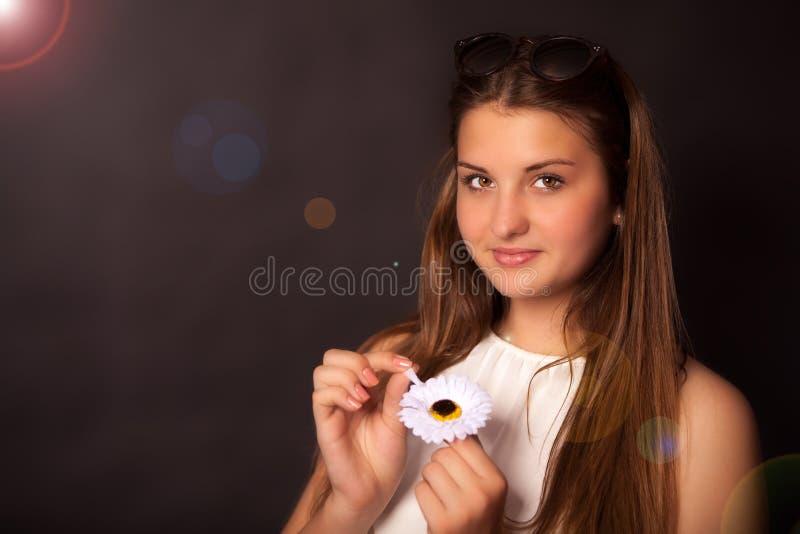 Ung flicka med en blomma och solexponeringsglas royaltyfria bilder