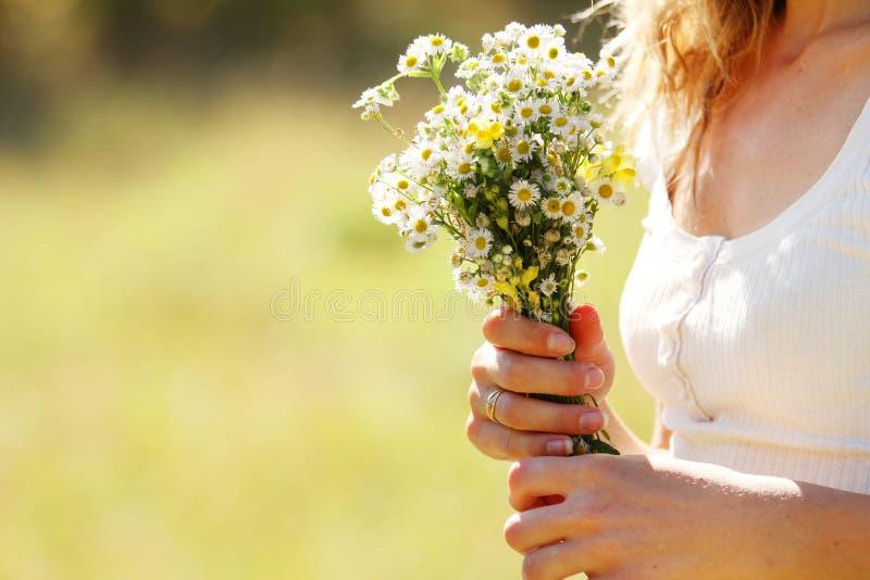 Ung flicka med en bukett av blommor i natur royaltyfria bilder