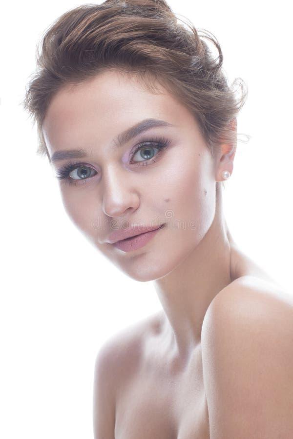 Ung flicka med en försiktig näck makeup och frisyr Den härliga modellen med glänsande gör perfekt hud Skönhet av framsidan royaltyfri fotografi