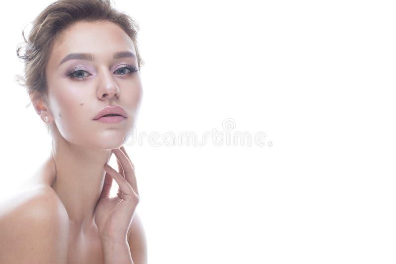 Ung flicka med en försiktig näck makeup och frisyr Den härliga modellen med glänsande gör perfekt hud Skönhet av framsidan arkivbild
