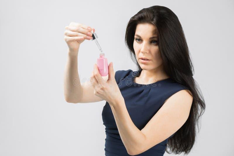 Ung flicka med en flaska av ansikts- serumomsorg som isoleras på vit bakgrund fotografering för bildbyråer
