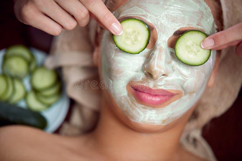 Ung flicka med en maskering för hudframsida royaltyfri bild