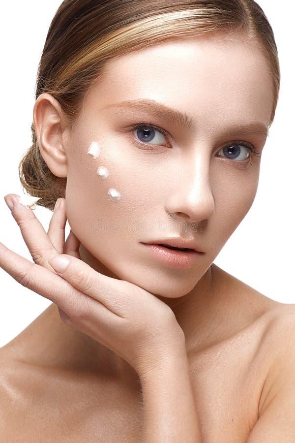 Ung flicka med en sund hud och nakenstudiemakeup Härlig modell på kosmetiska tillvägagångssätt med en kräm på hennes framsida royaltyfri foto