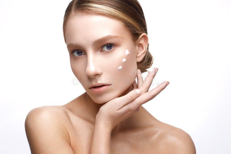 Ung flicka med en sund hud och nakenstudiemakeup Härlig modell på kosmetiska tillvägagångssätt med en kräm på hennes framsida royaltyfria bilder