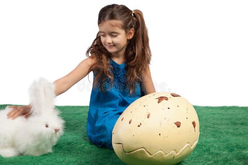 Ung flicka med ett enormt ägg formar och toy kaninen arkivbild