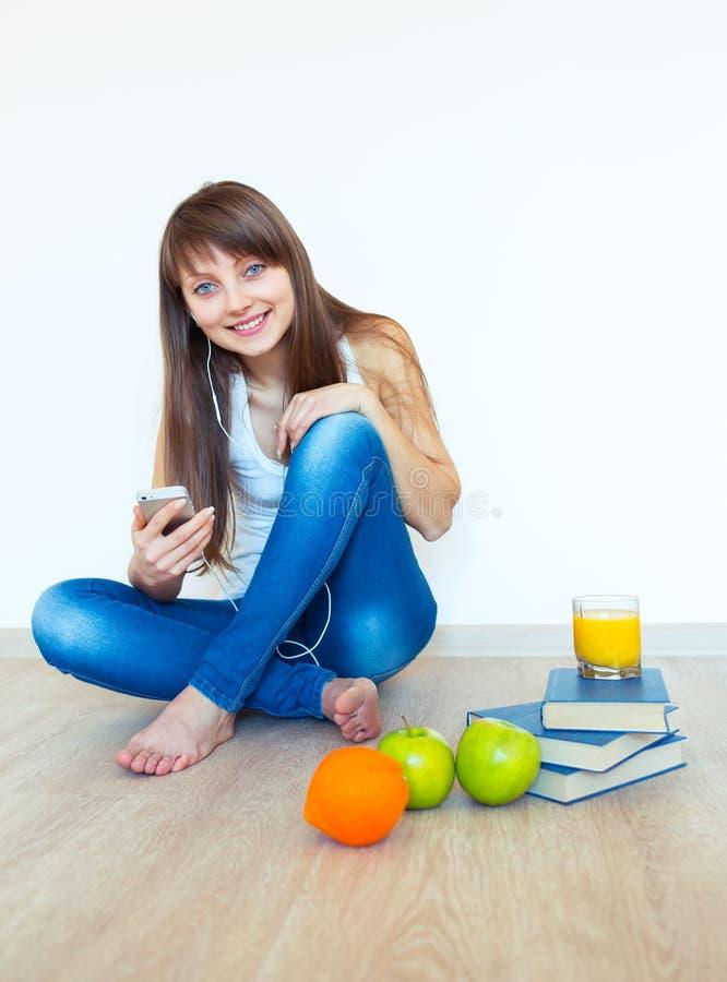 Ung flicka med hörlurar och lyssnande musik för grönt äpple på ho royaltyfria bilder
