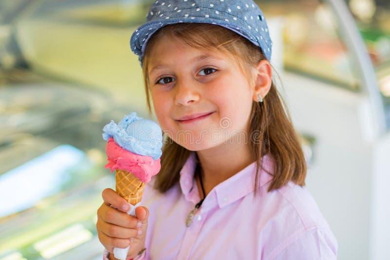 Ung flicka med hatten som äter det fria för en glass arkivbild