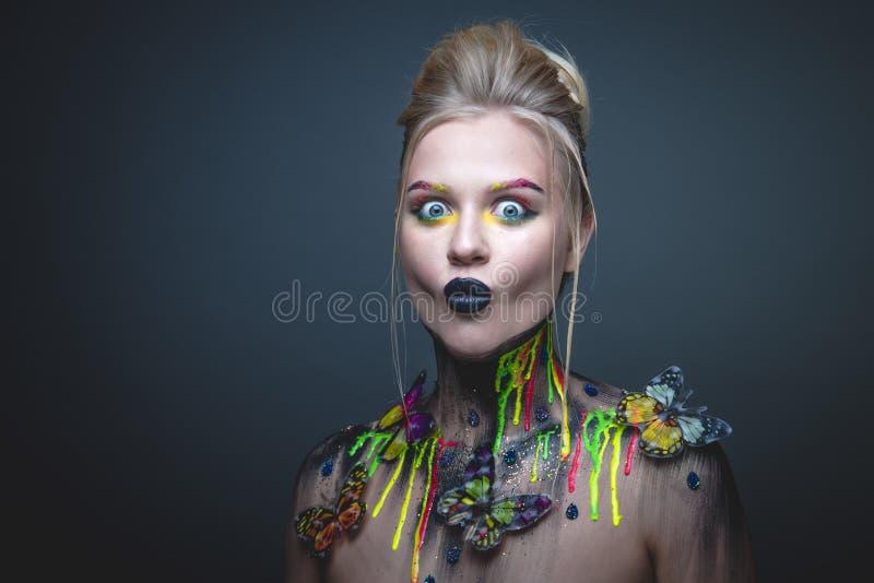 Ung flicka med idérik makeup med fjärilar royaltyfri foto