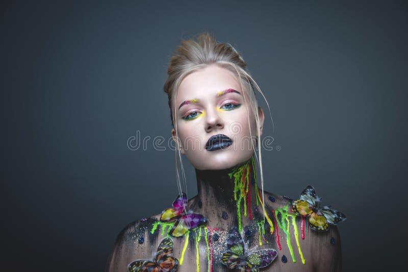 Ung flicka med idérik makeup med fjärilar royaltyfri bild