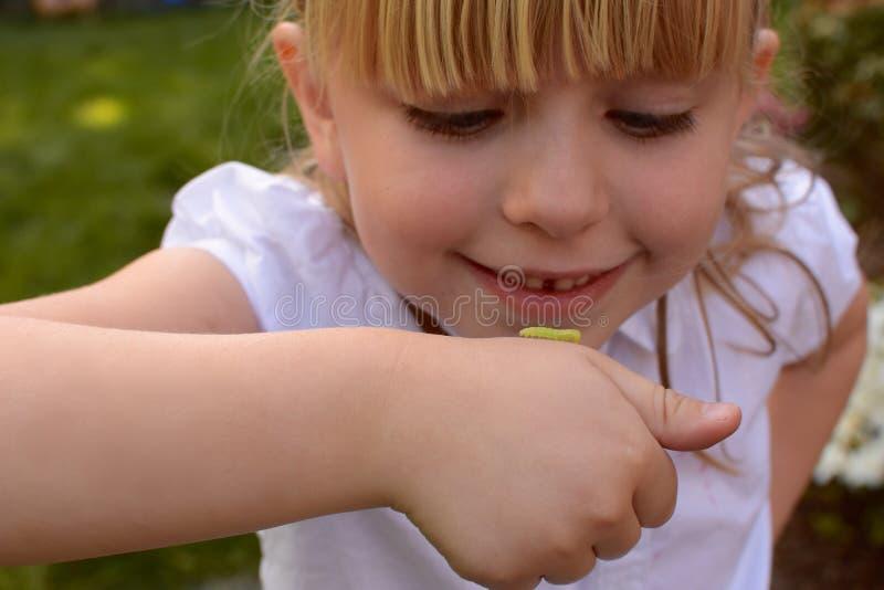 Ung flicka med inchwormen arkivfoto