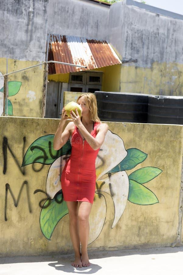Ung flicka med kokosnötter arkivbilder