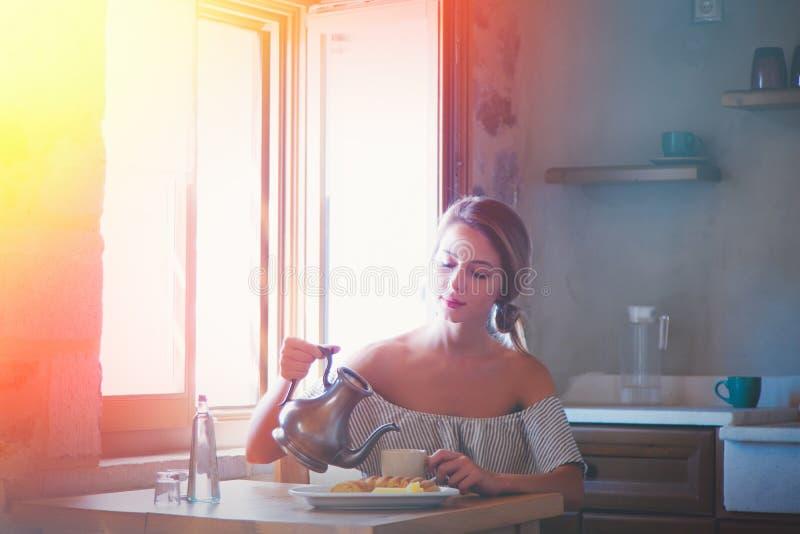 Ung flicka med koppen kaffe eller te på grekiskt kök royaltyfria foton