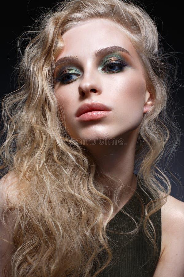 Ung flicka med krullning och ljust idérikt smink Härlig modell i örhängen och gräsplanöverkant Skönhet av framsidan arkivfoton