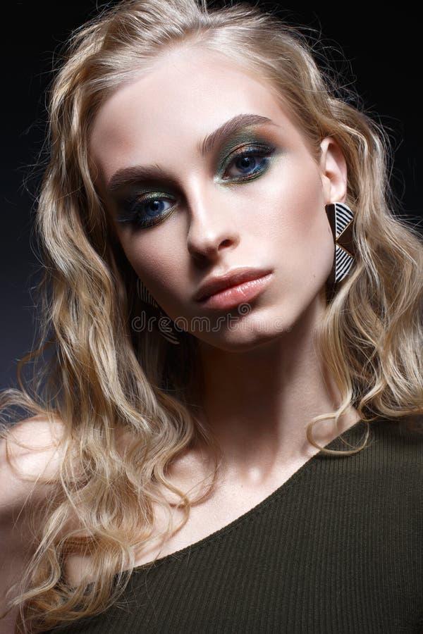 Ung flicka med krullning och ljust idérikt smink Härlig modell i örhängen och gräsplanöverkant Skönhet av framsidan royaltyfri foto