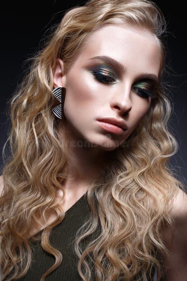 Ung flicka med krullning och ljust idérikt smink Härlig modell i örhängen och gräsplanöverkant Skönhet av framsidan royaltyfria bilder