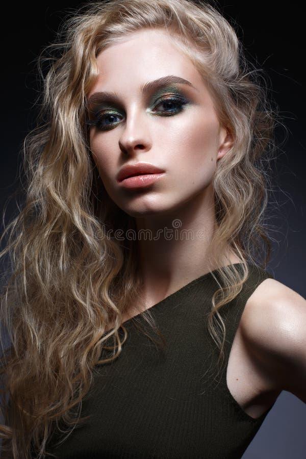 Ung flicka med krullning och ljust idérikt smink Härlig modell i örhängen och gräsplanöverkant Skönhet av framsidan royaltyfri bild