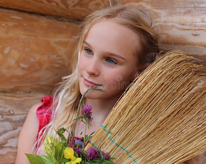 Ung flicka med kvasten och blommor arkivfoto
