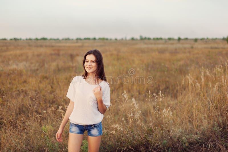 Ung flicka med långt brunt håranseende på höstängen royaltyfria foton