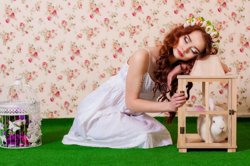 Ung flicka med långt hår med vit kanin royaltyfri foto