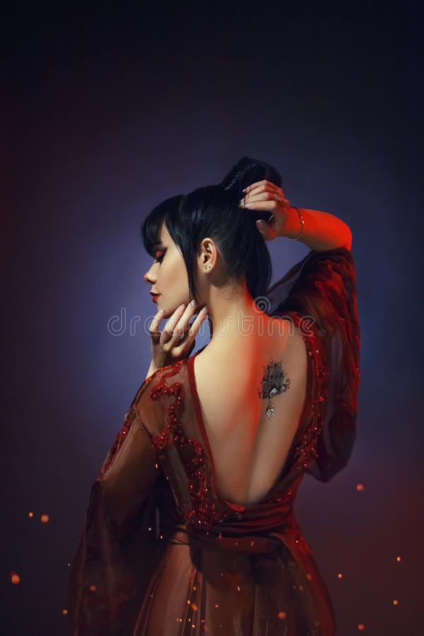 Ung flicka med mörker - blått hår och en smäll i en lång röd klänning med öppet naket gör bar tillbaka en tatoobildlotusblomma me royaltyfri bild