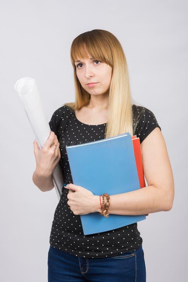 Ung flicka med mappar och en rulle av papper i händer av ledset se framåtriktat royaltyfri fotografi