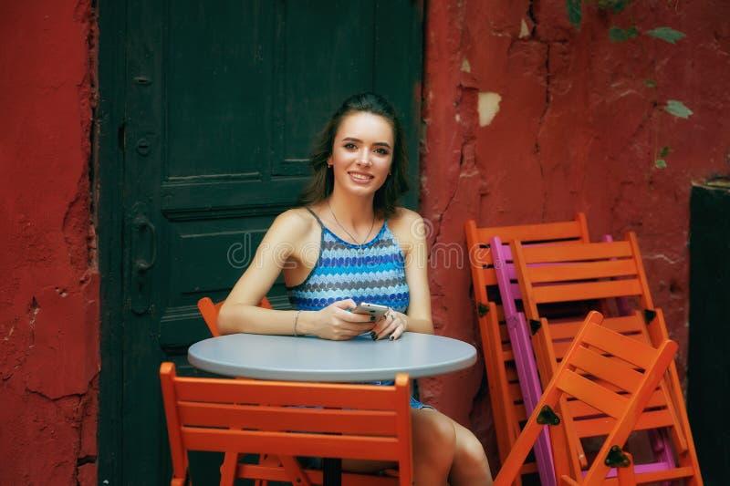 Ung flicka med mobiltelefonen i tappningkafé royaltyfria foton