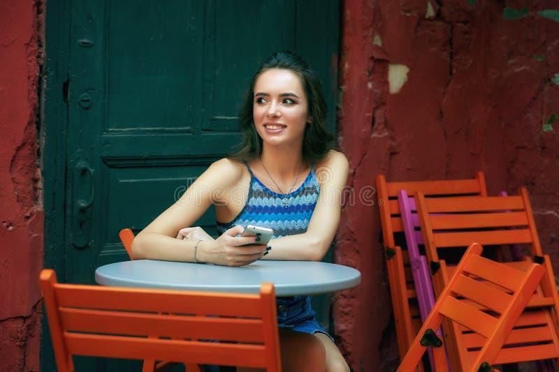 Ung flicka med mobiltelefonen i tappningkafé arkivbilder