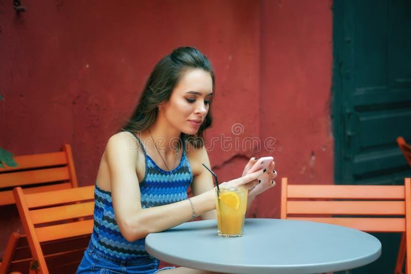 Ung flicka med mobiltelefonen i tappningkafé arkivfoto