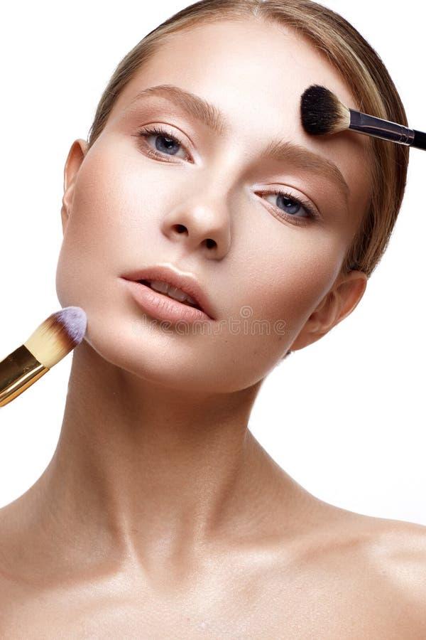 Ung flicka med perfekt glänsande hud- och nakenstudiemakeup En härlig modell med ett fundament och borstar för kosmetiska tillväg royaltyfria bilder