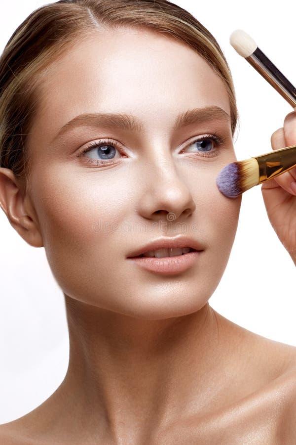 Ung flicka med perfekt glänsande hud- och nakenstudiemakeup En härlig modell med ett fundament och borstar för kosmetiska tillväg arkivfoto