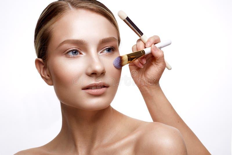 Ung flicka med perfekt glänsande hud- och nakenstudiemakeup En härlig modell med ett fundament och borstar för kosmetiska tillväg royaltyfri bild