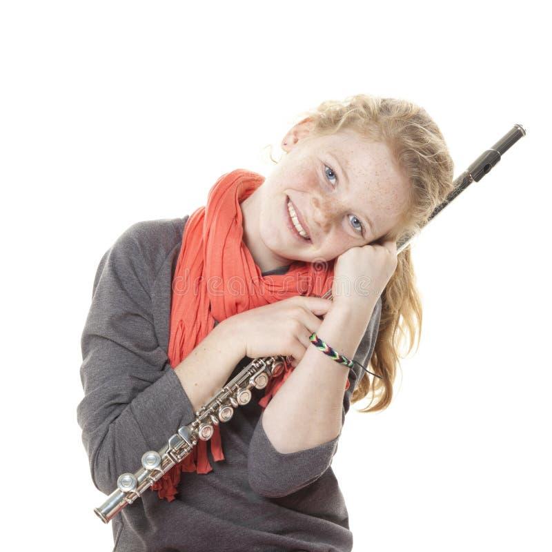 Ung flicka med rött hår och fräknar som rymmer flöjten i studio royaltyfria foton