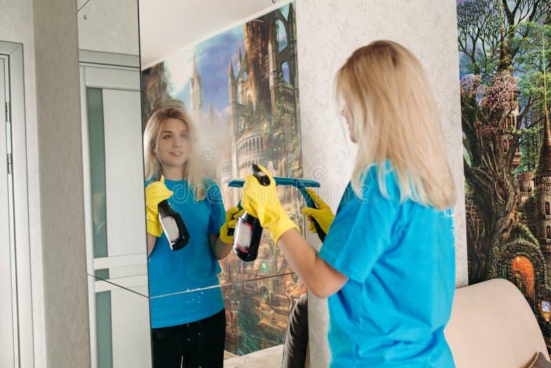 Ung flicka med special renande sprej och borste, tvättande spegel i rum arkivfoto