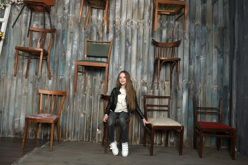 Ung flicka med stolar royaltyfri fotografi