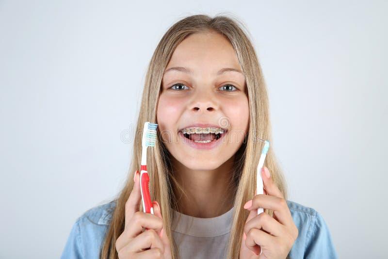 Ung flicka med tand- hänglsen royaltyfri bild