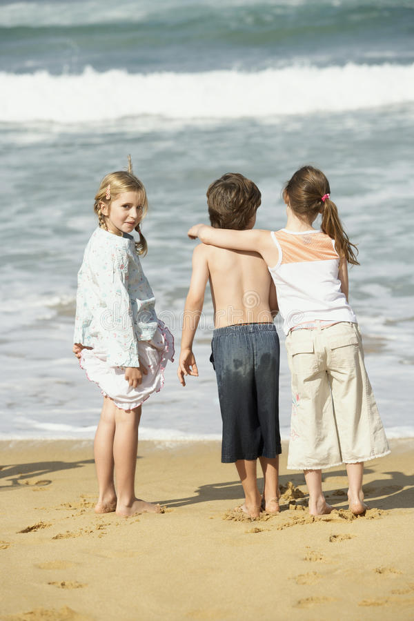 Ung flicka med vänner på stranden arkivfoton